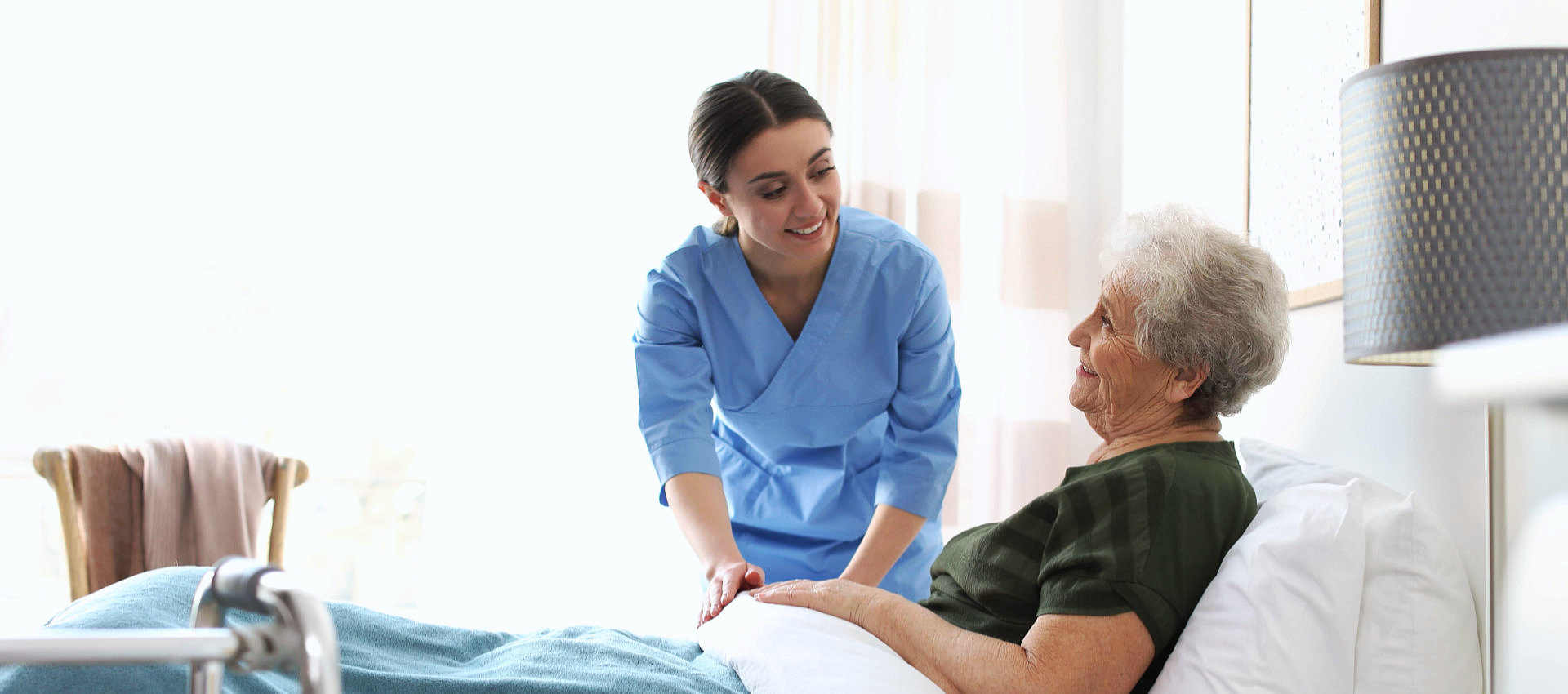 an elderly woman on a bed with a caregiver woman