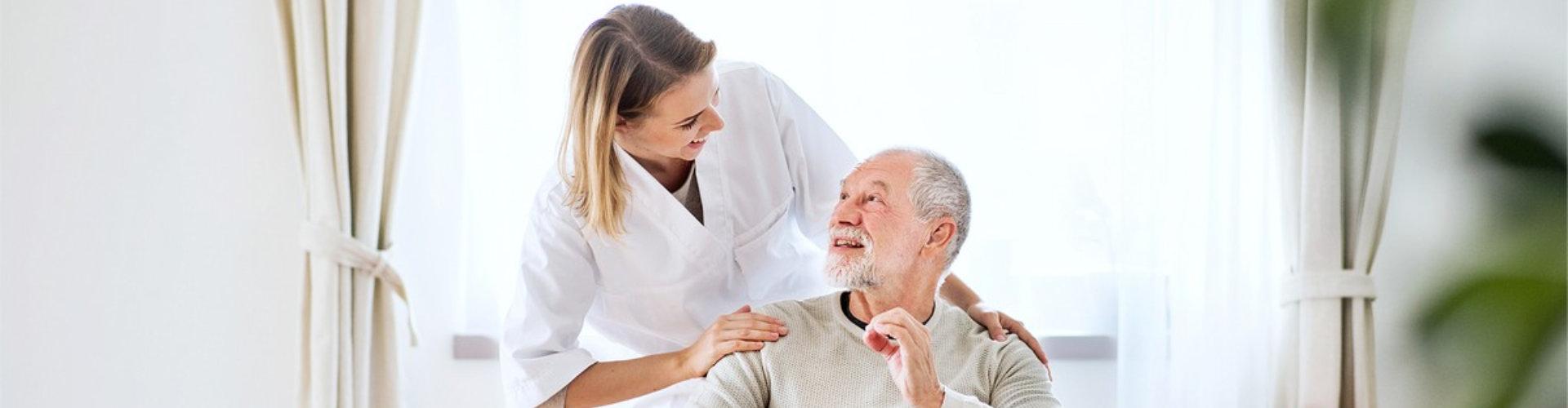 female caregiver hugging senior man