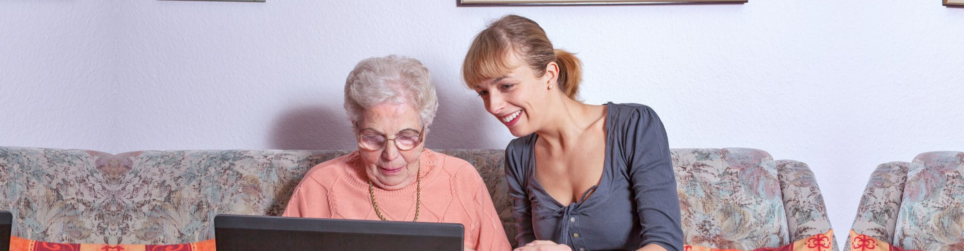 caregiver assiting senior woman in using a computer
