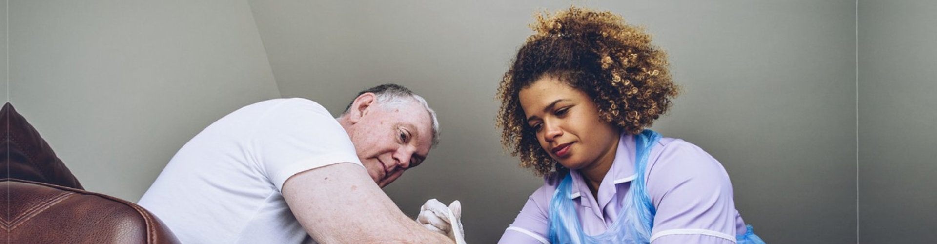 caregiver assisting senior man in cleaning