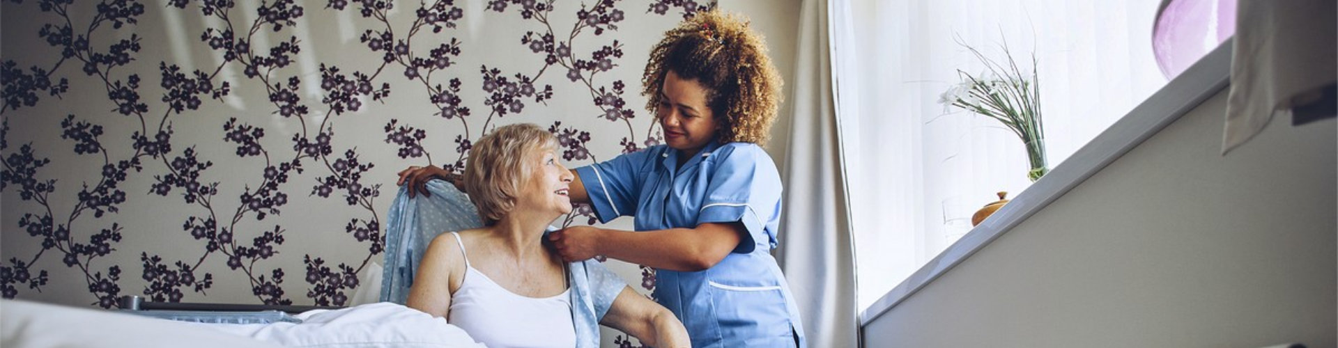 female caregiver assisting senior woman to dress up