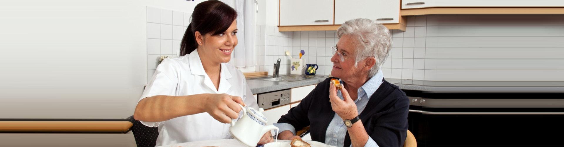 caregiver serving a food to senior woman